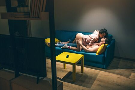 Young couple have intimacy in kitchen in night. Sexy shirtless man lying on sofa and kissing woman. She stand on knees above him. Sensual moment. Together in room.
