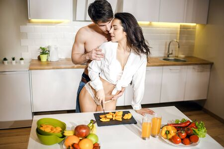 Young sexy couple after intimacy in kitchen in night. Hot seductive woman stand at table and cut fruit. Look back at shirtless guy and smile. Man stand behind her and lean forward.