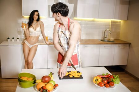 Young sexy couple after intimacy in kitchen in night. Cheerful haooy shirtless man in apron cut fruit and look back at woman. She wear white lingerie and hold juice glass in hand. Look at each other and smile.