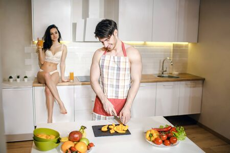 Young sexy couple after intimacy in kitchen in night. Careful well-built guy wear apron and cut fruit on desk. Beautiful hot woman sit on table with legs crossed and look at man. Stock fotó