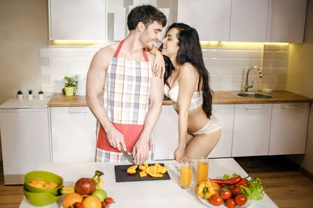 Young sexy couple after intimacy in kitchen in night. Cheerful people stand close and smile. Guy in apron. Hot seductive woman in whuite lingerie touch nose of man. Stock fotó