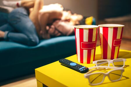 Young couple have intimacy in kitchen in night. Blurred background. Popcorn buckets with cinema glasses and remote control on table. Man on top. Hot sensual woman lying on sofa. Stock fotó