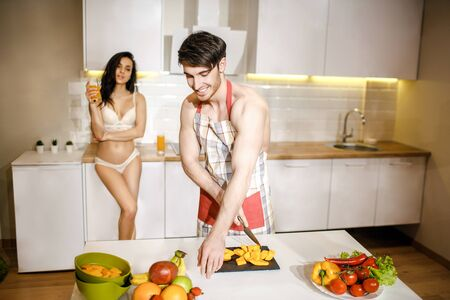 Young sexy couple after intimacy in kitchen in night. Handsome careful man cutting food on desk. Beautiful hot model stand on back in white lingerie. She hold glass of juice in hands and smile. Zdjęcie Seryjne