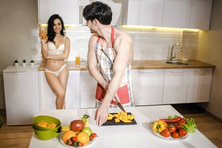Young sexy couple after intimacy in kitchen in night. Careful well-built shirtless man cut fruit and look bac at woman. She stand behind and hold glass of juice. Wearing sexy white lingerie