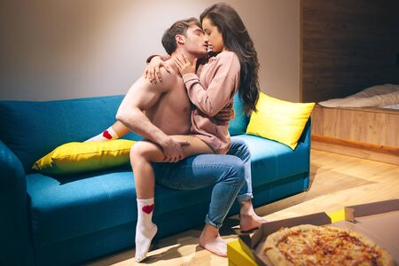 Young couple have intimacy in kitchen in night. Passionate shirtless man hold woman on his legs and kissing her. Seductive sensual model in sex position enjoying. Pizza on table.