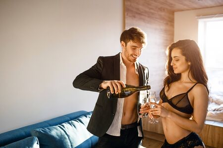 Young sexy couple in living room. Cheerful nice sexy man and woman after intimacy drinking sparkled wine. Guy pouring in into glasses. Smile and happiness.