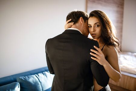 Young sexy couple in living room. Beautiful attractive young woman in black lingerie embrace man and look on camera. Businessman touch model with passion.