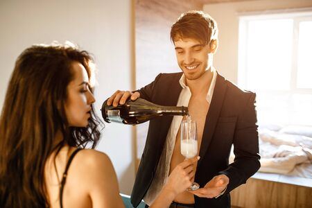 Young sexy couple in living room. Cheerful nice businessman in suit pouring sparkled wine into womans glass. Together in room. Sexy souple after intimacy. Zdjęcie Seryjne