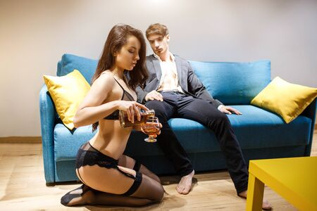 Junges Paar, das im Wohnzimmer hat. Mann in Jacke sitzt auf Sofa und schaut, wie Frau Alkohol in Glas gießt. Schönheit in schwarzen Dessous sitzt auf dem Boden. Meister und Sklave. Lust und Leidenschaft.