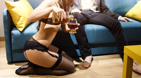 Young sexy couple in living room. Cut view of woman in black lingerie pouring wiskie into glass. Man sit on sofa in suit. Lust and passion. Zdjęcie Seryjne