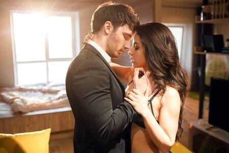 Pareja joven en la sala de estar. Imagen apasionada del hombre en traje y la mujer en lencería negra de pie muy juntos. Se tocan con los ojos cerrados. Momento asombroso.