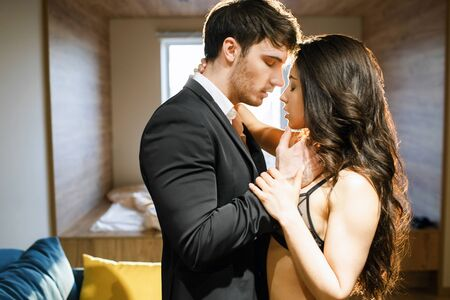 Young couple in living room. Businessman in suit touch woman in lingerie. Passionate moment. Lust, seduction and sensuality. BDSM, standing pose.