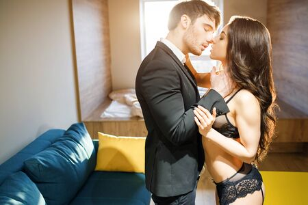 Young sexy couple in living room. Standing close to each other in passionate move. Businessman kissing prostitute. Sexy young woman in black lingerie very seductive and sensual. BDSM.