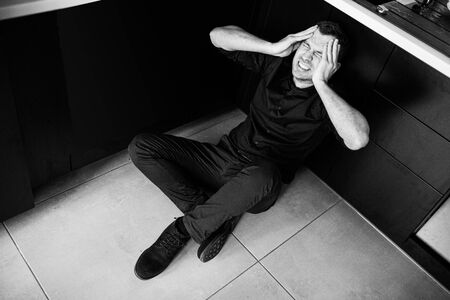 Black and white picture of young man in black clothes sitting separated alone in kitchen and scream. Hold hands on head and try to calm down. Disorder and pain. Desparation.