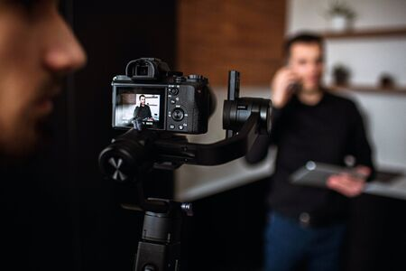 Picture with blurred background where young businessman stand in kitchen and talk on phone. Recording video of dusiness work call or meeting. Camera man stand behind camera and look to right.