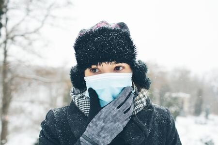 Young woman wear face mask for sickness coronavirus protection. Female person hold hand on it and think. Fear of sickness and infectioned body. Stand alone outside in warm clothes. Winter time. Stock Photo