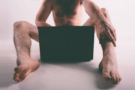 Young naked man watching pornography and masturbating 版權商用圖片