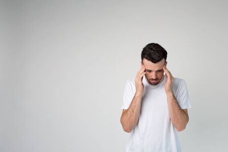 Young man isolated over background. Headache or thinking. Calm peaceful guy in studio stand alone and look down. Imagens