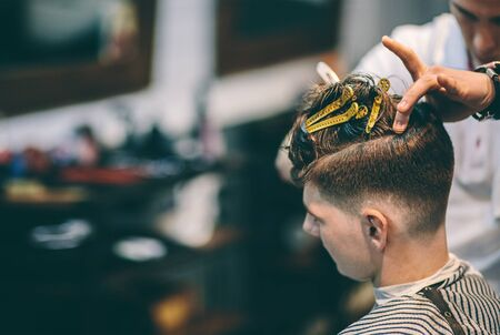 Hairdresser makes hairstyle a man with a clip on the head in a hairdressing salon
