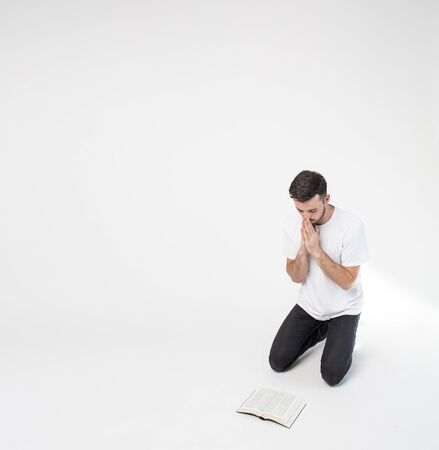 Young man isolated over background. Believer standing on knees in front Bible on floor and praying. Hold hands together and look down. Believe in God Savour, Jesus Christ.