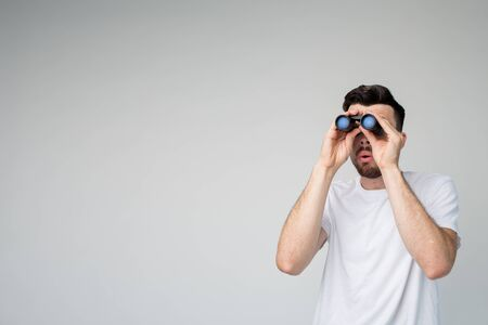 Young man isolated over background. Guy look a binoculars far away forward. Stand alone in studio. Casual looking guy on picture. Investigating.
