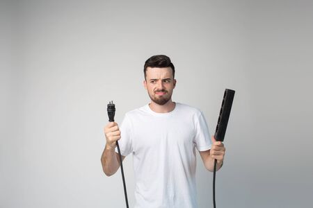 Young man isolated over background. Guy hold socket in hands with boy and girl output. Look on camera serious angry and unhappy. Guy stand alone in studio. Repair time.