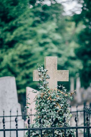 Vertical picture of old stone cross on grave or cementary. Daylight and green trees on blurred background. 写真素材 - 143406416
