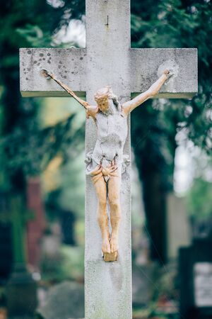Picture of old wooden or stone cross with figure of crucified Jesus Christ. Memory on grave or cementary. Green trees on background. Daylight. 写真素材
