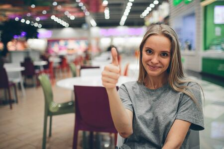 Cheerful lovely young woman showing thumbs up in a food court with an unfocused background