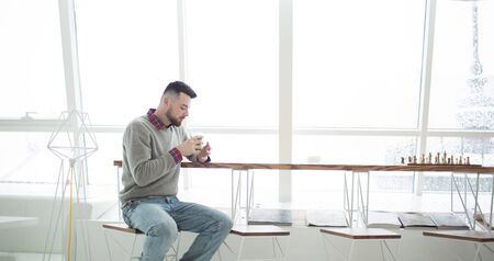 Young bearded man in cafe. He dressed in gray sweater and blue jeans. Sits on high chair at long table near window. Man looked at cup in his hands. On table chessboard. Laconic interior.