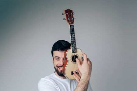Young man isolated over background. Portrait of guy cover face part with small ukulele. Musician and player have fun alone during posing 版權商用圖片