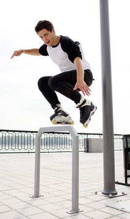 Picture of professional young man jumping during rollers skating outside on street. Urban view. Skating with obstacle. Jump up. Daylight.