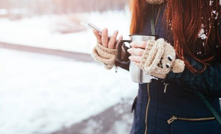 Winter. Woman with red hair wearing gloves . Girl drinking hot tea or coffee with iron insulated cup. It uses a phone or smartphone. Playing, loo king for something on the Internet. Scrolls news feed.