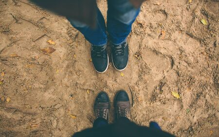 Man and woman stand opposite each other. Close up of feet in winter boots in the sand Stock Photo