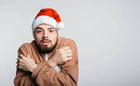 portrait of man dressed in pajamas i Christmas red hat in cold isolated 版權商用圖片