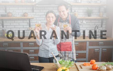 Cheerful couple stand together in kitchen. They hold glasses of wine and look on laptop. People smile. They have vegetables on table.