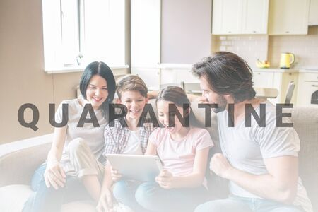 Happy family is sitting on sofa. Girl holds tablet in hands. She is excited and amazed. All members of family are looking at it.