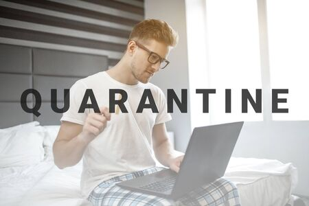 Serious young man sit on bed this morning. Guy wear pajama and glasses. He hold credit card in hand and type on laptop keyboard.