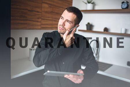 Young etrepreneur or businessman talking on phone or has business conversation. Sand in kitchen alone with tablet in hands. Manage company or business. Look to left. Concentrated and confident man. 版權商用圖片