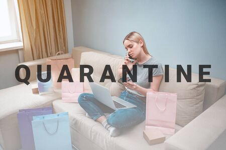 Online shopping at home. Young blonde shopper with laptop and credit cards is ordering by smarthphone in online shop while sitting on a sofa with shopping bags