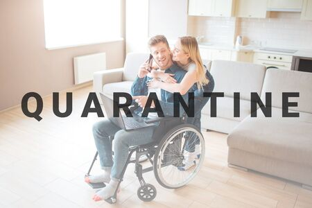 Young man with special needs together with beautiful woman. He sit in wheelchair and hold laptop. She stand behind and lean to him. Couple together in room.