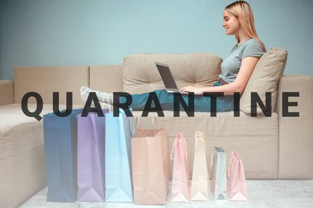 Online shopping at home. Young smiling woman is sitting on sofa and using laptop near colorful shopping bags