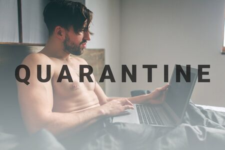 Naked bearded dark-hair Serious casual young man using laptop in bed at home