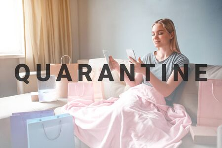 Online shopping at home. Young blonde woman with tablet and smartphone is comparing prices of goods in online shop while sitting with blanket on a sofa 版權商用圖片