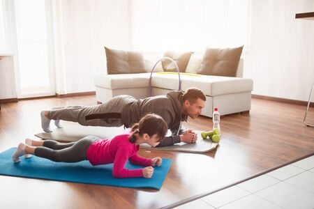 father and daughter are training at home. Workout in the apartment. Sports in home conditions. They make the doing plank. Фото со стока