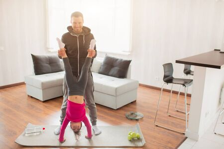 young father and his cute little daughter have workout at home. Handstand push-up. Cute kid is standing on hands. They wear in sportswear and have exercises