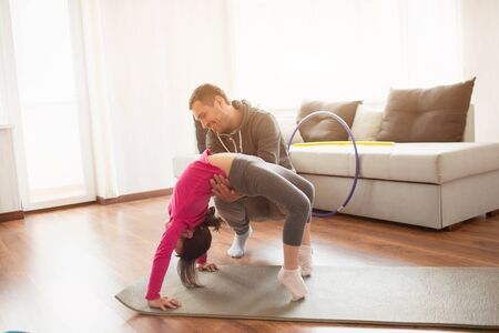 father and daughter are training at home. Workout in the apartment. Sports at home in bridge pose. 版權商用圖片