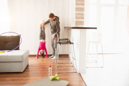 young father and his cute little daughter have workout at home. Handstand push-up. Cute kid is standing on hands. They wear in sportswear and have exercises near the window in room