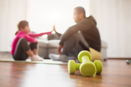 father and daughter are training at home. Workout in the apartment. Sports at home. They sit on yoga mats and give each other five. In the foreground there are dumbbells Фото со стока