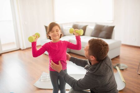 father and daughter are training at home. Workout in the apartment. Sports at home. They are standing on a yoga mat. Girl holding dumbbell